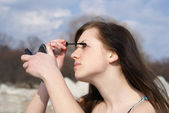 Attractive young girl making makeup — Stock Photo