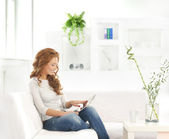 Young attractive woman with a tablet in modern interior — Stock Photo