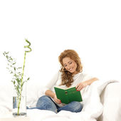 Young beautiful woman reading book on the sofa — Stock Photo