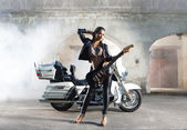 Sexy female biker with a guitar — Stock Photo