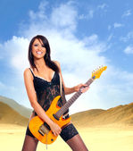 Sexy brunette with the guitar over desert background — Stock Photo