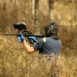 Paintball player with marker on forest game — Stock Photo