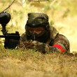 Paintball player with marker on forest game - ストック写真