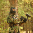 Paintball player with marker on forest game - Foto Stock