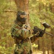 Paintball player with marker on forest game - Stock Photo