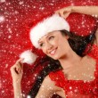 Young sexy Santa over red background with  snow — Stock Photo