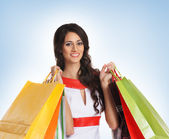 Young beautiful woman with some shopping bags isolated on blue — Stock Photo