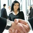 Stock Photo: Group of business over futuristic background with blury handshae in front