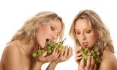 Young beautiful woman eating grapes — Stock Photo
