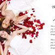 Young and healthy girls over white silk and rose petals — Stock Photo #16167055