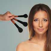 Studio photo of make-up process over grey background — Stock Photo