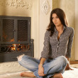 Stock Photo: Attractive womnear fireplace