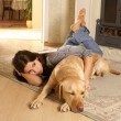 Stock Photo: Attractive womwith labrador dog on flor