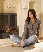 Attractive woman near the fireplace — Stock Photo