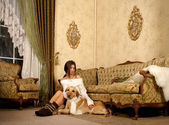 Attractive woman with the labrador dog in the luxury interior — Stock Photo