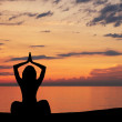 Silhouette of young woman doing yoga exercise over the sunset background — Stock Photo #21487549