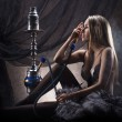 Young sexy woman in luxury underwear smoking the hookah — Stock Photo #21487979