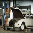 Young sexy woman repairing the retro car - Stock Photo