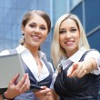 Foto Stock: Two young attractive business women looking to the laptop