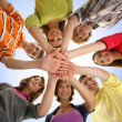Foto Stock: Group of smiling teenagers staying together and looking at camer