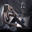 Stock Photo: Young sexy womin luxury underwear smoking hookah