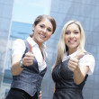 Two young attractive business women demonstrate the success — Foto de Stock