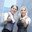 Two young attractive business women demonstrate the success — 图库照片