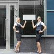 Two young attractive business women are showing the blank banner — Stok fotoğraf