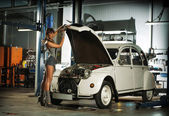 Young sexy woman repairing the retro car — Foto Stock