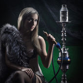 Young sexy woman in luxury underwear smoking the hookah — Stock Photo