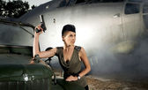 Young attractive female soldier with the plane and car — Stock Photo