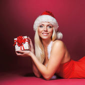 Young sexy Santa over red background — Stock Photo