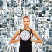 Young attractive woman showing the clock isolated on white — Stock Photo
