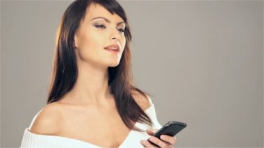 Young attractive brunette girl typing a text message on her mobile phone over grey background — Stock Video