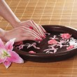 Beautiful female hands with flowers and petals in spa style - Photo