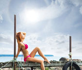 Young sexy woman in swimsuit relaxing on the pier — Stock Photo