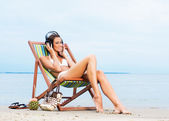 Sexy woman listening to the music on the beach — Stock Photo