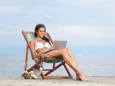 Sexy woman with the notebook pc relaxing on the beach — Stock Photo