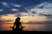 Silhouette of young woman doing yoga exercise over the sunset ba — Stock Photo