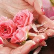 Beautiful female hands with flowers and petals — Stock Photo