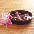 Ceramic bowl with some flowers and petals - Stock Photo
