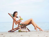 Sexy woman eating grapes on the beach — Stock Photo