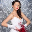 Stock Photo: Young and beautiful bride standing with the flower bouquet