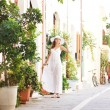 Young and beautiful lady walking down the ancient street — Stock Photo #25309737