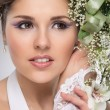 Young and beautiful bride standing with the flower bouquet — Stock Photo #25309849