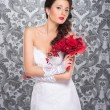 Young and beautiful bride standing with the flower bouquet - Stockfoto