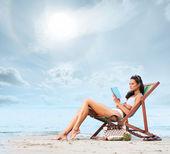 Giovane, bella, sportiva e sexy donna leggendo sulla spiaggia — Foto Stock