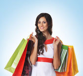 Young beautiful woman with some shopping bags isolated on white — Stock Photo