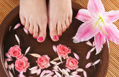 Spa background with a beautiful legs, flowers, petals and ceramic bowl — Stock Photo