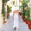 Young and beautiful lady walking down the ancient street — Stock Photo